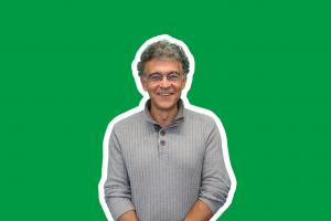vor grünem Hintergund steht der Leiter der RK Oberbayern Schneider-Velho